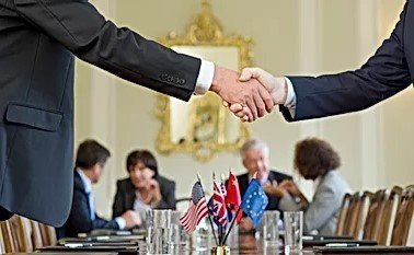 Two Men in Suits Shaking Hands Over Flag Centerpiece in International Conference Setting