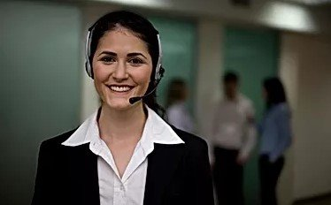 Woman in the Foreground Smiling with Headset On