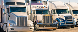 Four Semi Trucks Parked in a Line on a Dirt Lot